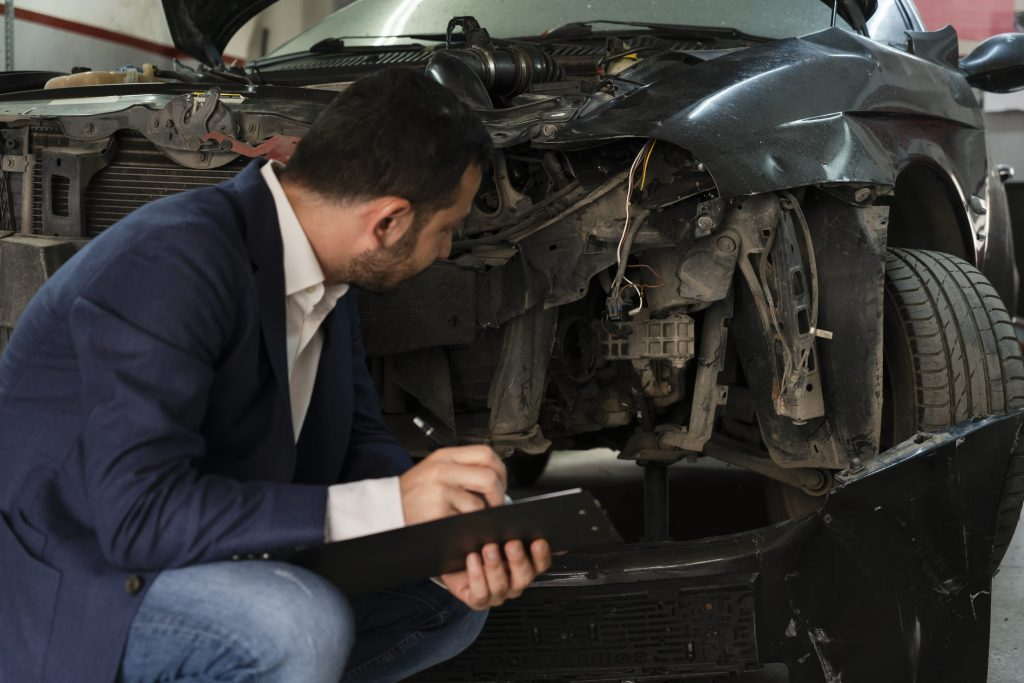 insurance adjuster inspecting damage after an accident