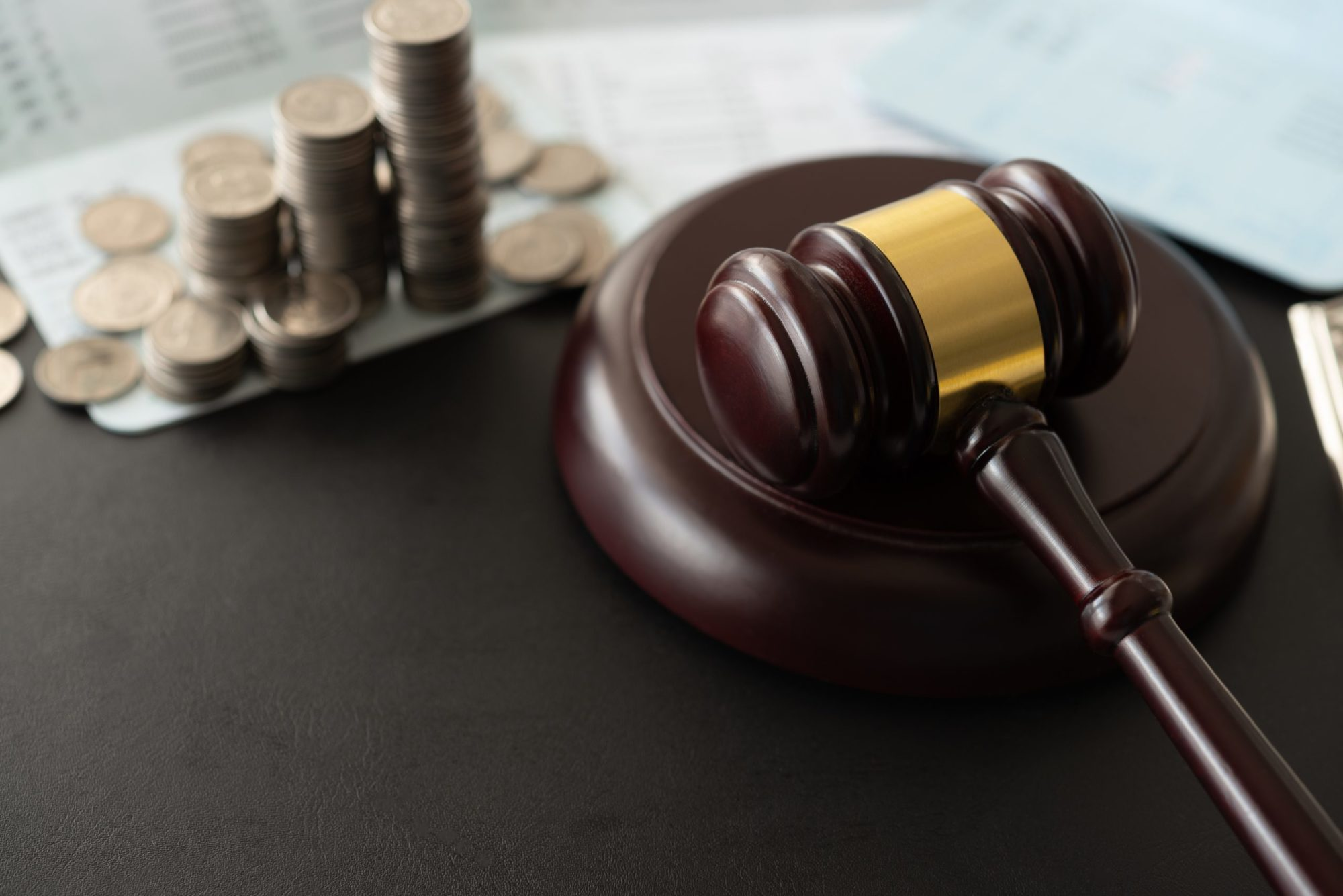 gavel next to a pile of coins