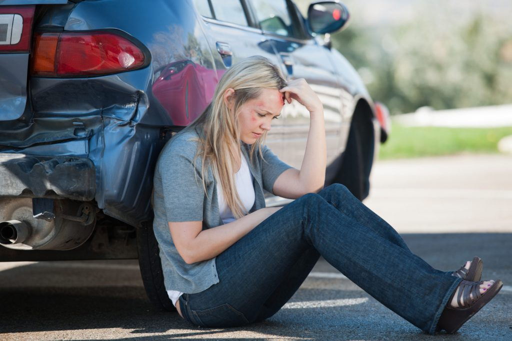 Female Accident Victim Waits Outside of Her Car