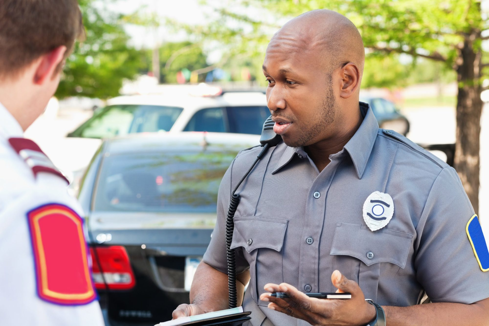 Police officer speaking with people after car accident