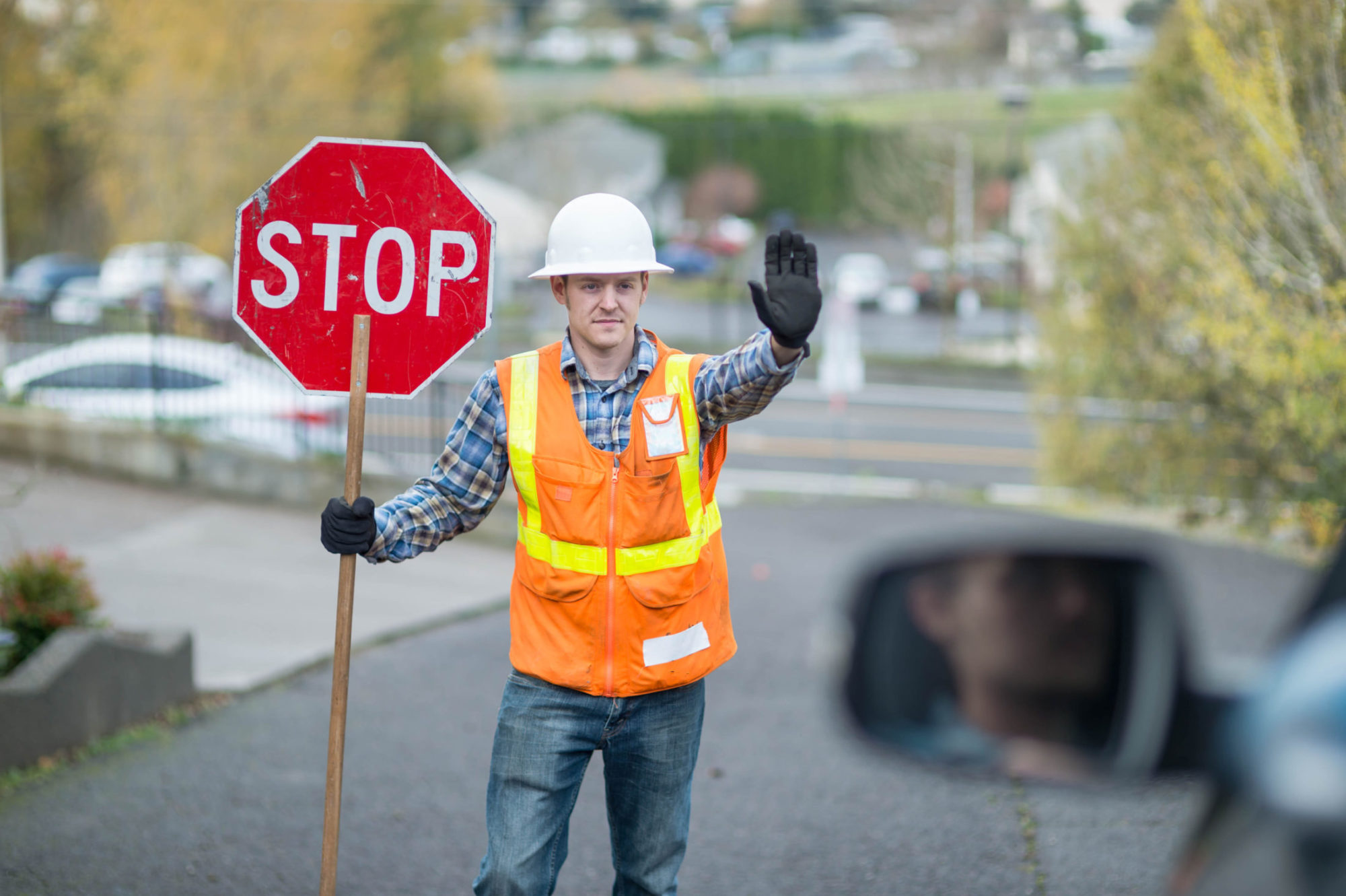 Flagger holds up stop sign for traffic in construction zone