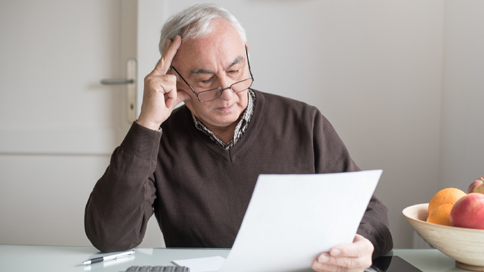 Elderly Man Reviewing His Finances Alone Stock Photo