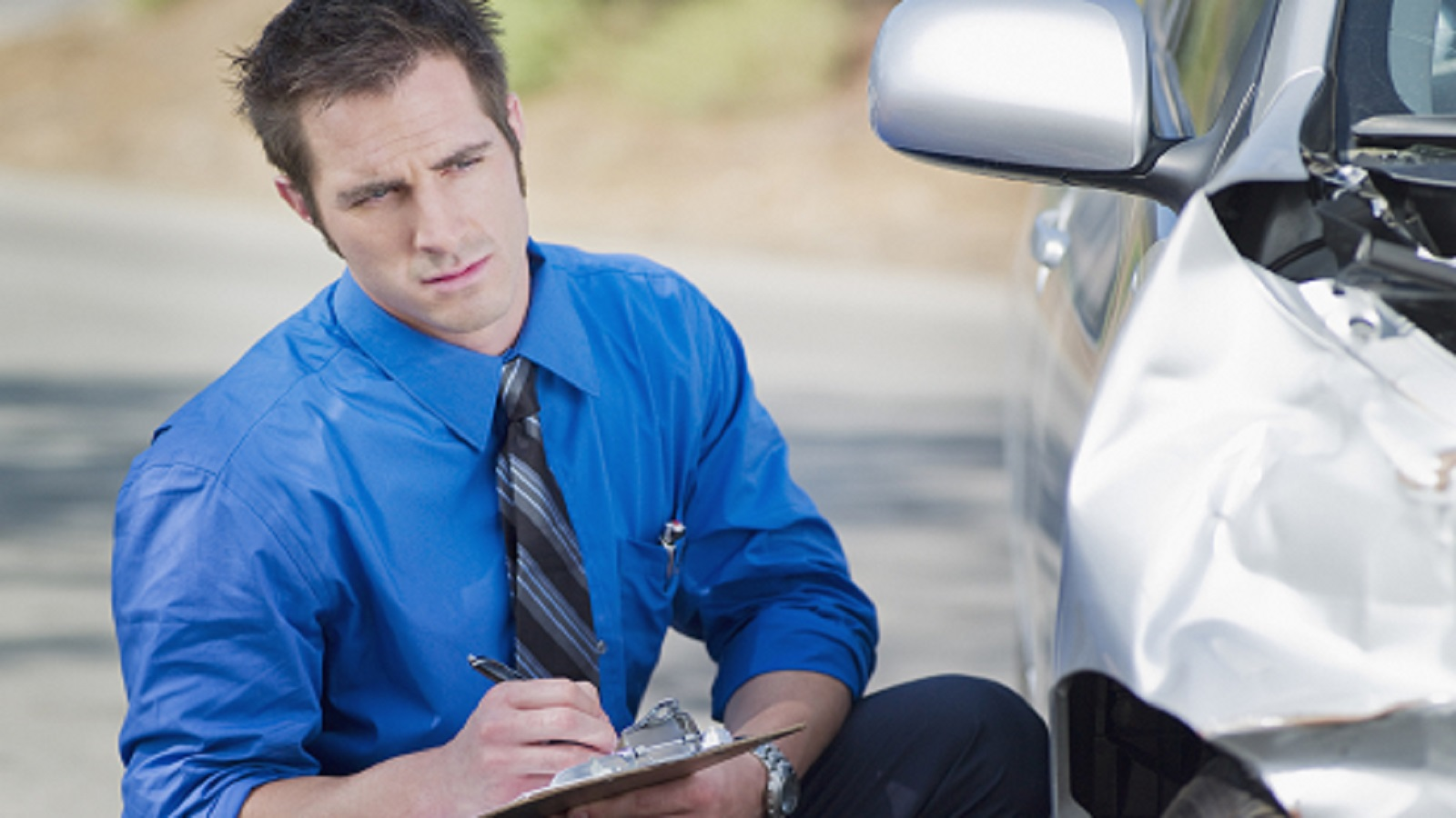 Insurance Adjuster Examining Car Accident Stock Photo