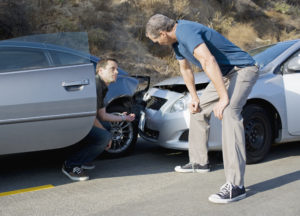 two men examining the damage after an Oklahoma City car accident
