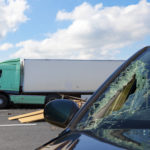 A damaged car in the aftermath of a big truck accident.